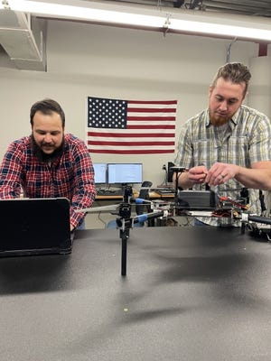 Berry Aviation intern Thomas Blehm and engineer Aron Felder integrate a drone for a defense customer at Berry Aviation's Unmanned Aerial Systems shop in Stillwater. Both are OSU aerospace graduates. [PHOTO PROVIDED]