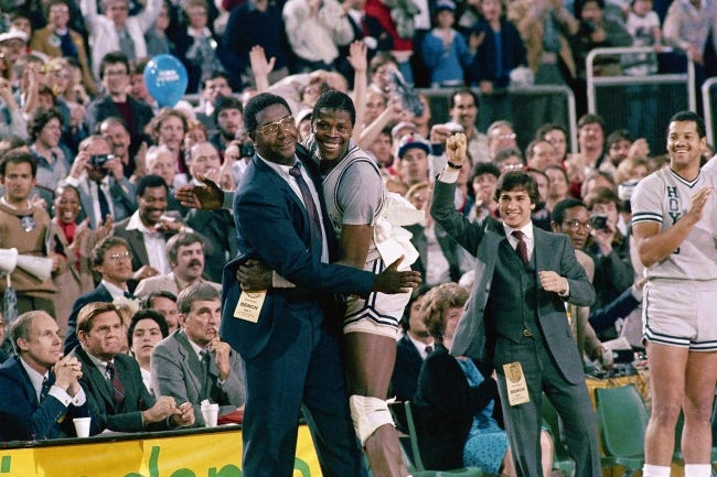 Georgetown head coach John Thompson, pictured hugging center Patrick Ewing after defeating Houston for the 1984 NCAA championship, was the first Black head coach to win the Division-I men's basketball title. He turned Georgetown into a powerhouse and opened doors for other Black coaches. He died last August at age 78. [AP Photo/File]