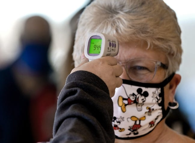 Members of IMMY Labs checks the temperature of a person arriving to the Covid-19 vaccination pod at the Embassy Suites by Hilton Norman Hotel & Conference Center in Norman, Okla. on Monday, Feb. 22, 2021. [Chris Landsberger/The Oklahoman]