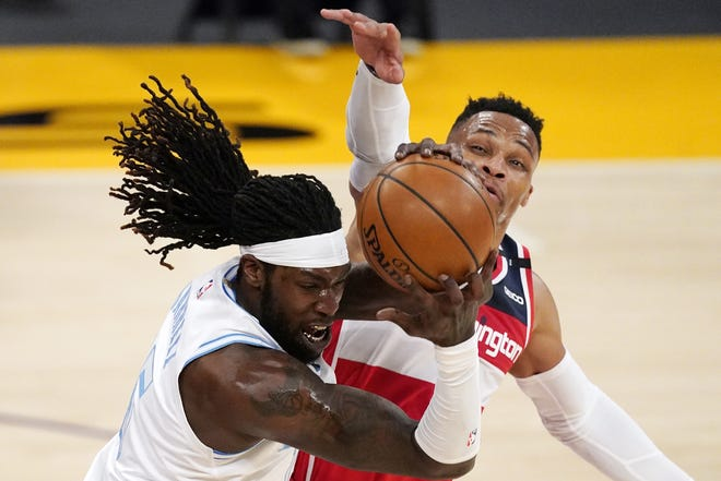 Lakers center Montrezl Harrell, left, grabs a loose ball away from Washington guard Russell Westbrook during the first half of a game in Los Angeles, Monday. Westbrook scored 32 points for the Wizards, who rallied from a 17-point deficit in the second half. [AP Photo/Mark J. Terrill]
