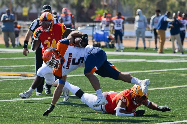 Langston running back Markel Scott tries to keep his balance in the Lions' season opener last Saturday. After Langston canceled all sports in the fall, the football team played for the first time in 462 days at Arizona Christian. [KEITH MOODY/ARIZONA CHRISTIAN]