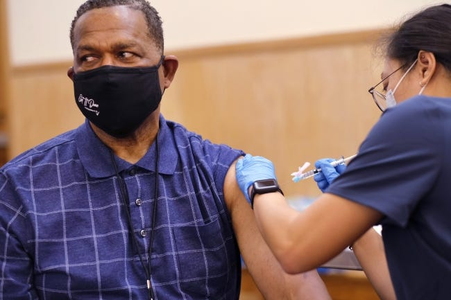 Bishop Jeffery Goldsmith, senior pastor of Emmanuel Tabernacle, receives his first dose of COVID-19 vaccine during a vaccination pod with OU Health at his church on Saturday. [Doug Hoke/The Oklahoman]
