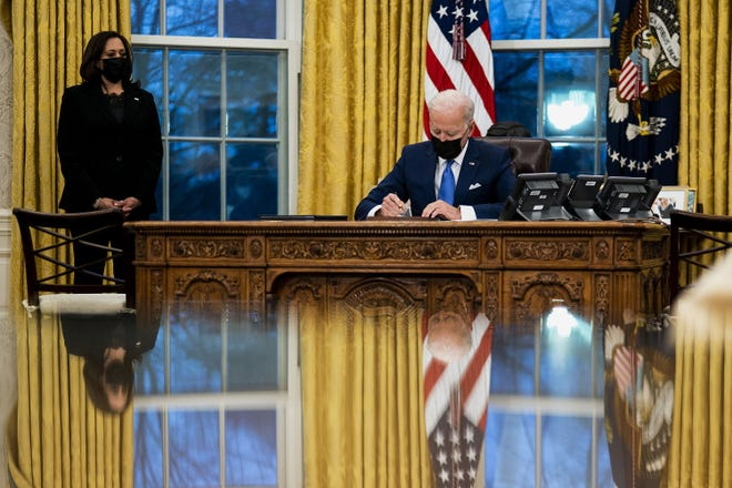 U.S. President Joe Biden signs several executive orders directing immigration actions for his administration as Vice President Kamala Harris looks on in the Oval Office at the White House in Washington on Feb. 2. [Doug Mills/Pool/Getty Images/TNS]