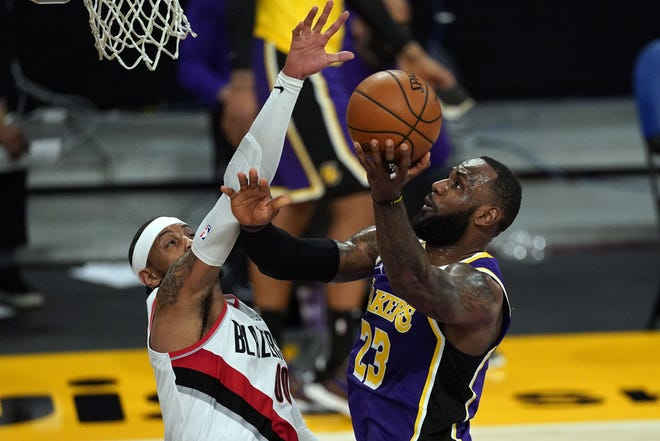 Lakers forward LeBron James (23) takes a shot against Trail Blazers forward Carmelo Anthony (00) during the first half of a game Friday in Los Angeles. [AP Photo/Mark J. Terrill]