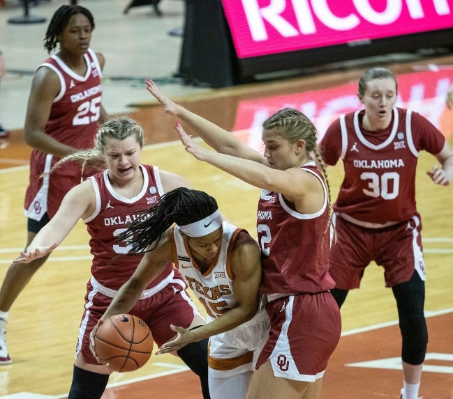 Texas' Kyra Lambert tries to get out of a trap by Oklahoma's Tatum Veitenheimer, left, and Gabby Gregory. [RODOLFO GONZALEZ/FOR AMERICAN-STATESMAN]