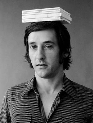 """Jerry McMillan's (U.S. b. 1936) photograph of """"Ed Ruscha with Six of His Books on His Head"""" is featured in the exhibit """"OK/LA"""" at the Fred Jones Jr. Museum of Art in Norman. [Image provided]"""