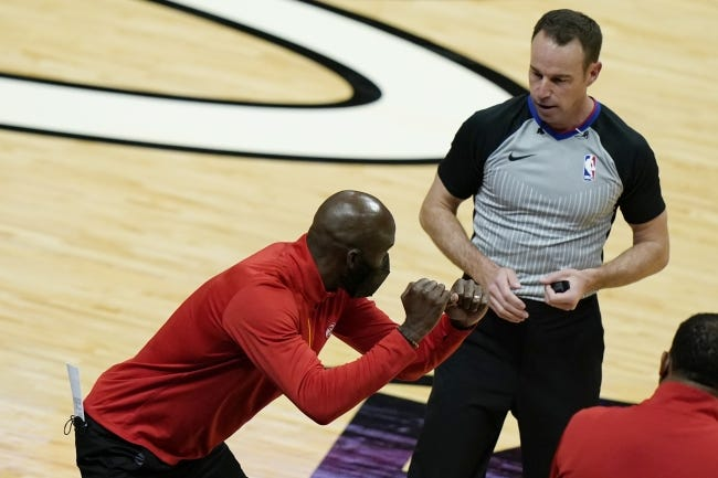 Atlanta Hawks head coach Lloyd Pierce, left, talks with official Josh Tiven during a game against the Heat in Miami on Sunday. Pierce was fired on Monday. [AP Photo/Lynne Sladky]