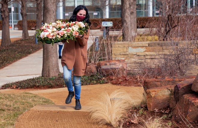 Above: Heather Cole carries a flower arrangement that was placed Monday at the Myriad Botanical Gardens in downtown Oklahoma City as part of the Floral Heart Project. The project is a COVID-19 memorial effort that will lay floral hearts in cities across the country in conjunction with a National Day of Mourning. Right: A flower arrangement shaped like a heart is placed Monday in the Scissortail Park North Lens garden for the Floral Heart Project in Oklahoma City. [Chris Landsberger photos/The Oklahoman]