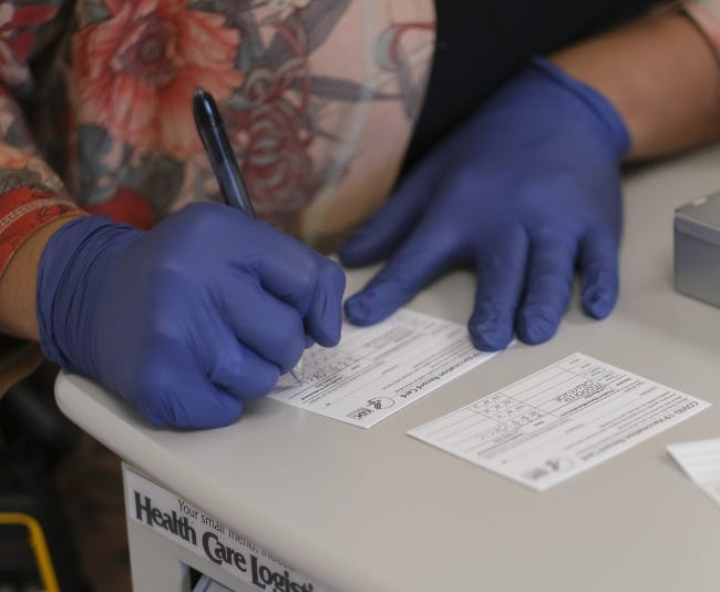 A health worker fills out a COVID vaccination card on Tuesday. [Doug Hoke/The Oklahoman]