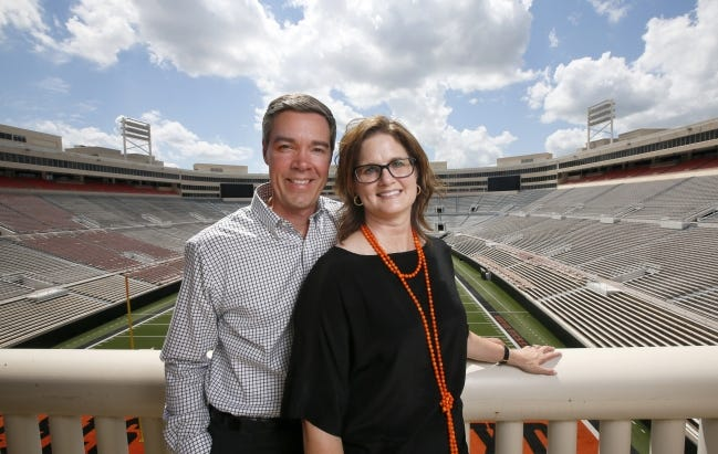 Chad Weiberg and his wife, Jodi Weiberg, pose for a photo at Boone Pickens Stadium in 2017. Chad Weiberg will be introduced as the new OSU athletic director Thursday.
