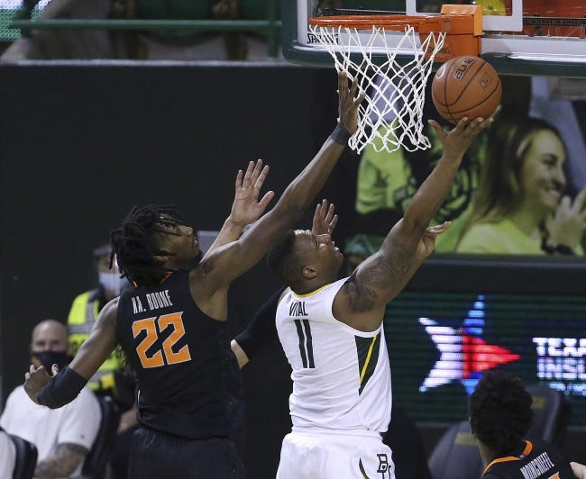 Baylor guard Mark Vital, right, scores past Oklahoma State forward Kalib Boone on Thursday. OSU travels to West Virginia on Saturday to close out the regular season. [AP Photo/Jerry Larson]