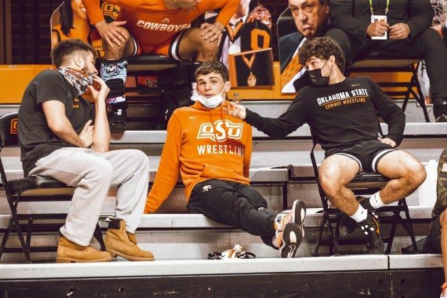 OSU wrestler Kaden Gfeller, left, talks with teammates Boo Lewallen, middle, and Daton Fix during the Cowboy Challenge Tournament on Feb. 14 at Gallagher-Iba Arena in Stillwater. [Bruce Waterfield/OSU Athletics]