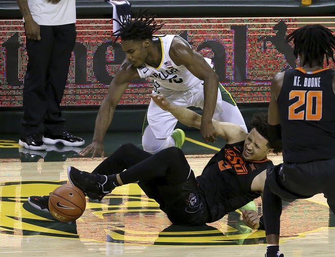 Oklahoma State guard Cade Cunningham, bottom, injures his ankle as he and Baylor guard Davion Mitchell reach for the loose ball in the second half Thursday night during OSU's 81-70 loss. Cunningham's status for Saturday's game at West Virginia is up in the air. [AP Photo/Jerry Larson]