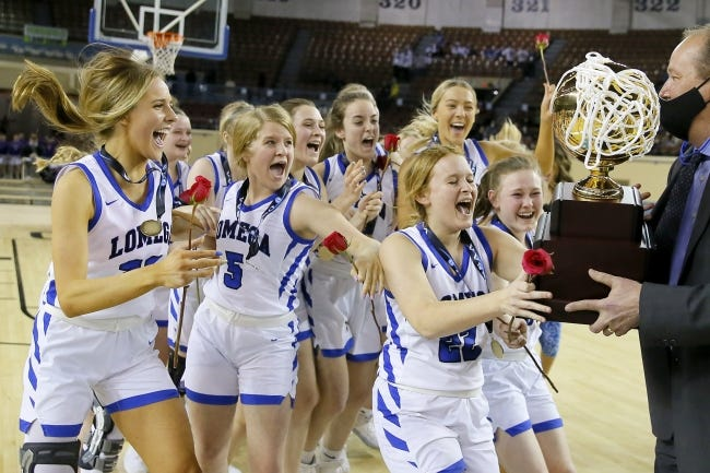 Lomega players collect their trophy after winning the Class B girls high school basketball state championship game between Lomega and Kiowa in State Fair Arena at OKC Fairgrounds in Oklahoma City, Saturday, March 6, 2021. [Bryan Terry/The Oklahoman]