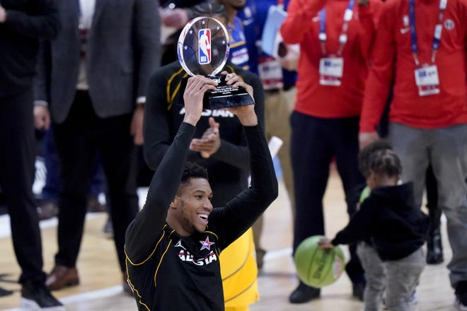 Milwaukee Bucks forward Giannis Antetokounmpo holds up the MVP trophy after the NBA All-Star Game in Atlanta on Sunday. [AP Photo/Brynn Anderson]