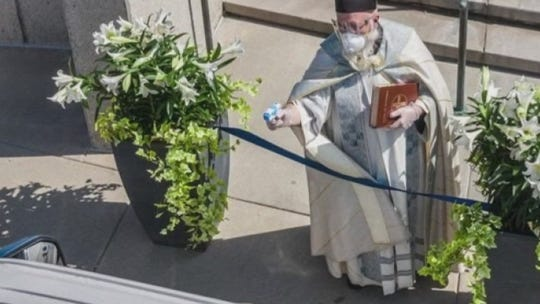 Detroit priest goes viral after using squirt gun with holy water to bless parishioners