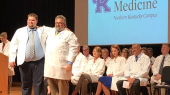 University of Kentucky College of Medicine's inaugural Northern Kentucky Campus class of 35 students includes a man who was given the white coat of a doctor by his father Dr. Mike Kalfas in during a ceremony witnessed by families at NKU.