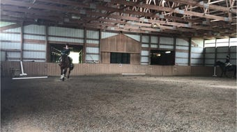 Members of the Foxmoor Equestrian Team practice riding horses inside the riding facility at Foxmoor Farm in Horseheads.