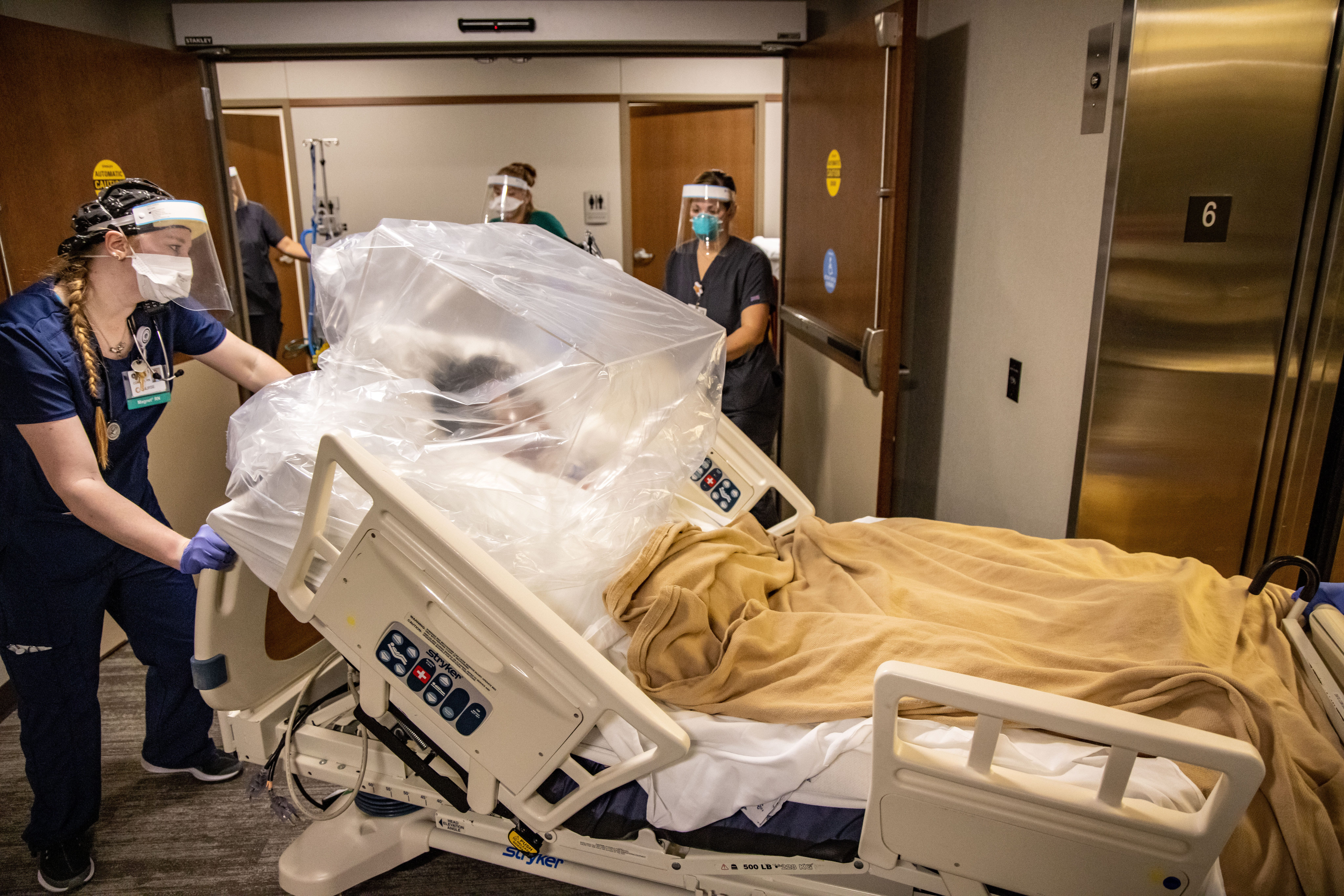 A nurse at Mary Greeley pushes a patient's bed to take them from the 6th floor COVID-19 unit to the ICU.
