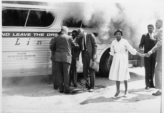 Freedom Riders exit bus firebombed in Anniston, Alabama, by Ku Klux Klan-led mob on May 14, 1961. The riders were challenging segregations laws in the South.