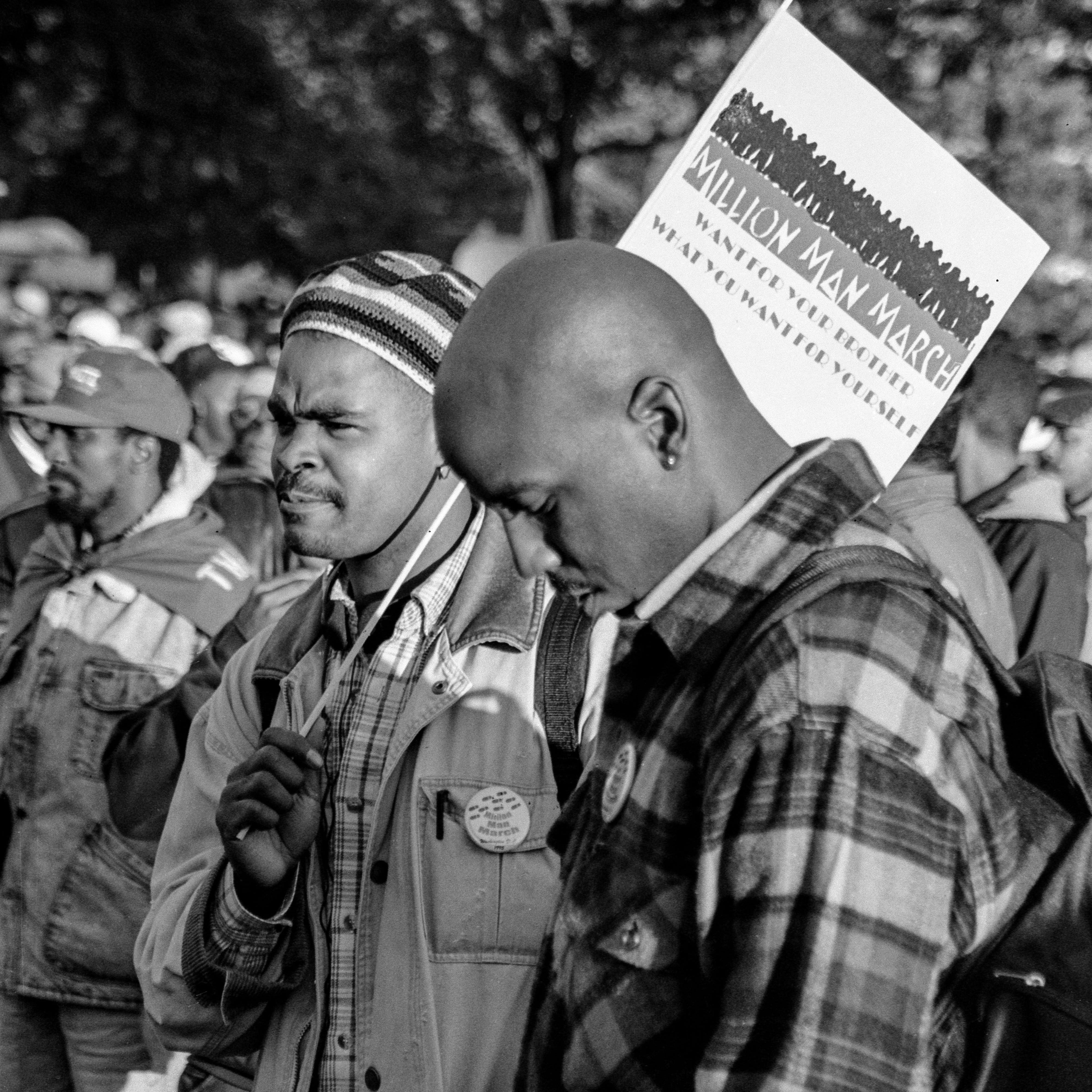 A man at the 1995 Million Man March in Washington, D.C., bows his head while others look on during an event that was billed as 'A Day of Atonement.'