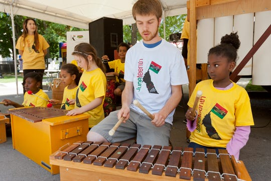 Ian Cummings of Ithaca, center, and Gabrielle, Barrett, 8, right, both of Ithaca, perform with the Southside Afterschool Music Program at the center's Juneteenth celebrations in 2016.