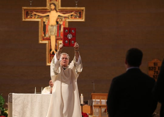 Deacon Bill Richer prepares to preach the Gospel during Christmas Eve Mass at St. Francis Catholic Church in West Des Moines on Wednesday, Dec. 24, 2014.