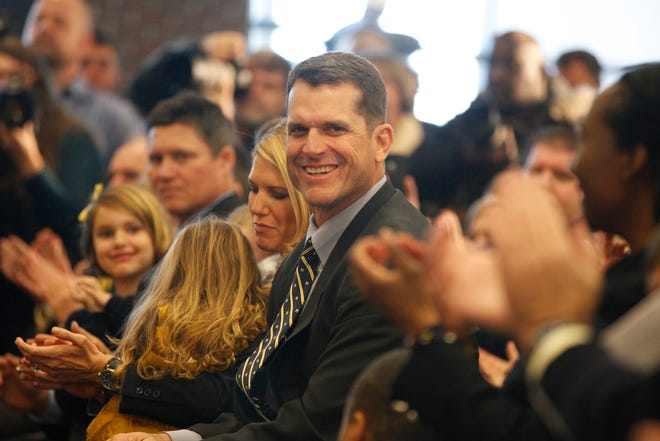 Jim Harbaugh smiles as he is introduced as the next Michigan football head coach, while sitting with his wife and family during a news conference in Ann Arbor on Dec. 30, 2014.