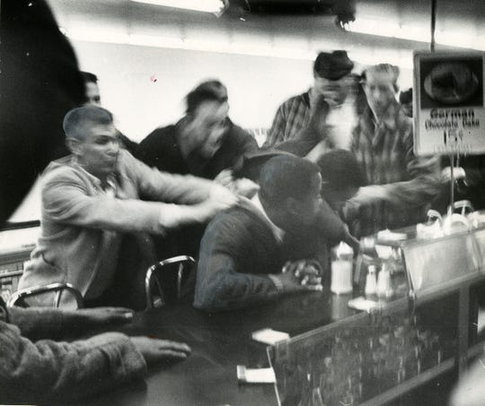 John Lewis is pulled off a stool during a sit-in at a segregated lunch counter in Nashvillle in the 1960s.