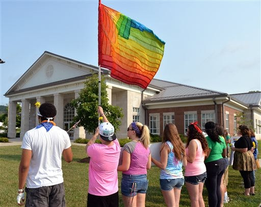 Protesters waive a rainbow flag on the front lawn of the Rowan County Judicial Center, Tuesday, June 30, 2015, in Morehead, Ky. The protest was being held against Rowan County Clerk Kim Davis, who, due to the ruling of the Supreme Court of the United States and her own religious beliefs, has refused to issue any marriage licenses in the county. (AP Photo/Timothy D. Easley)
