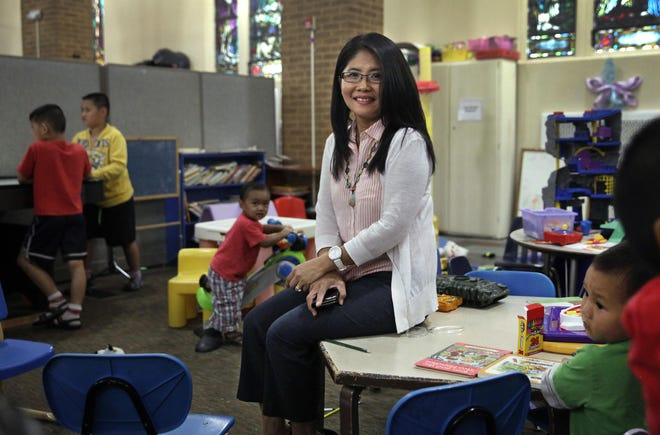 Hkadin Lee sits in the children's area of St Mary's Place refugee center where she is a services coordinator. Lee came to this country from Burma in 1990 and shared her story with StoryCorps.
