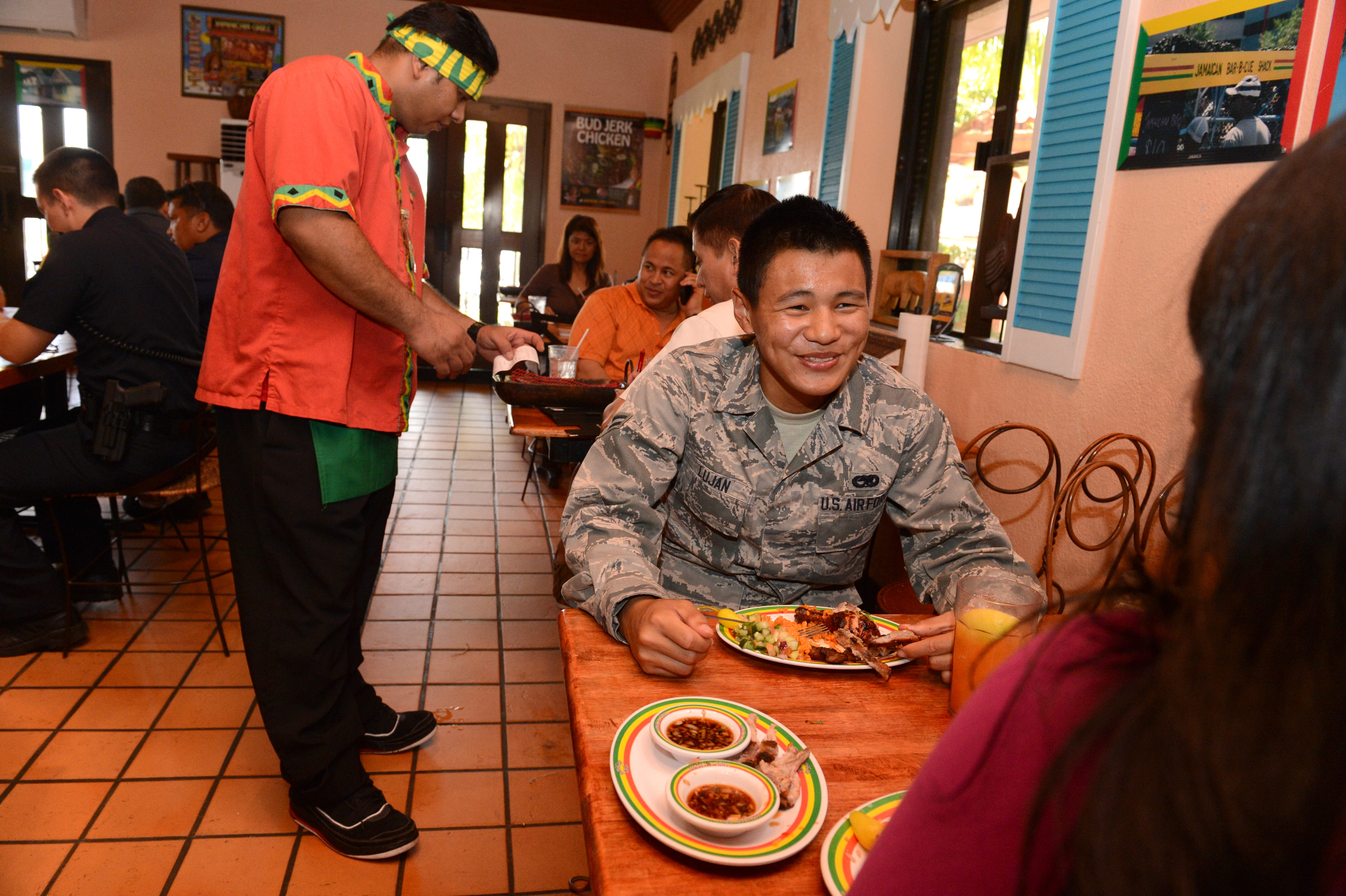 Airman 1st Class Patrick Lujan smiles as he enjoys lunch with his mother, Jae Medina, at the Jamaican Grill in Hagåtña on Sept. 11, 2012. Jamaican Grill is one of 40 island restaurants that took a pledge Wednesday to remove salt and other condiments from their tables to reduce the risk of heart disease on Guam.