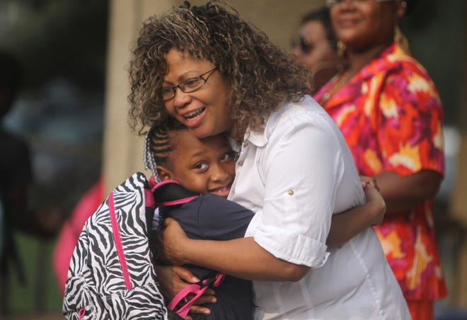 Tajhae Powell, a third grader, greets Lauretta Works, a paraprofessional at the school, with a big hug.