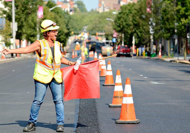 Eleanor Lavelle, of Jans Flagging, Inc., based in Harrisburg, works to control traffic while crews work to pave West Market Street in downtown York, Pa. on Tuesday, Sept. 8, 2015.
