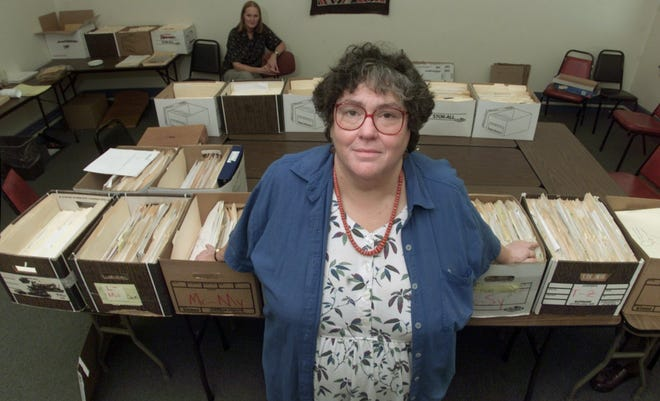 Attorney Elizabeth Fink poses in the Greater Upstate Law Project offices in downtown Rochester in August of 2000, surrounded by the hundreds of claims by former Attica inmates made after the prison riots.