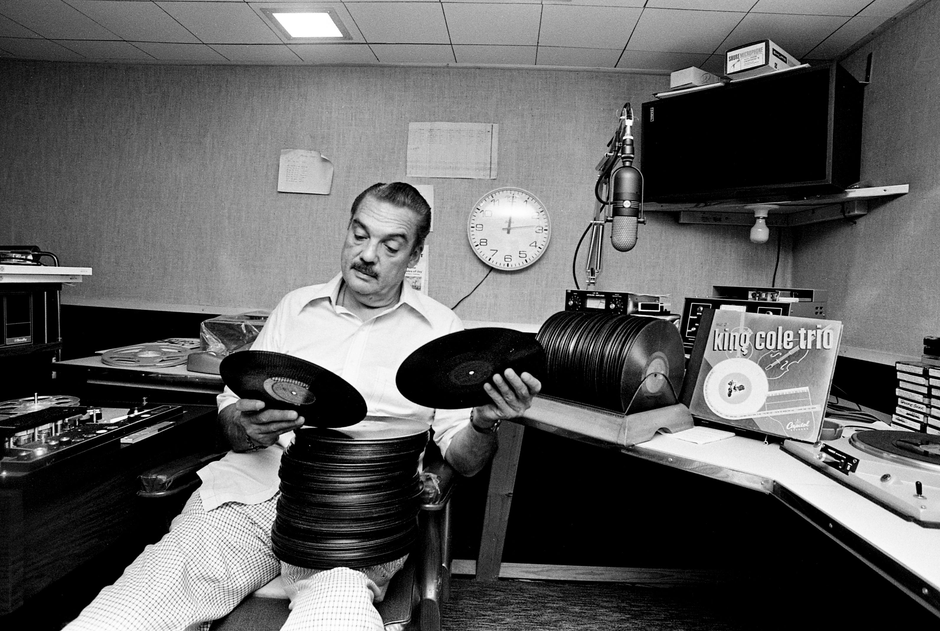 Bill Allen of WLAC Radio muses in his home studio Sept. 6, 1975, over one of several stacks of big band era records to be auctioned at the Symphony Guild Street Fair. The collection of 200 discs was valued at a minimum of $1,500.