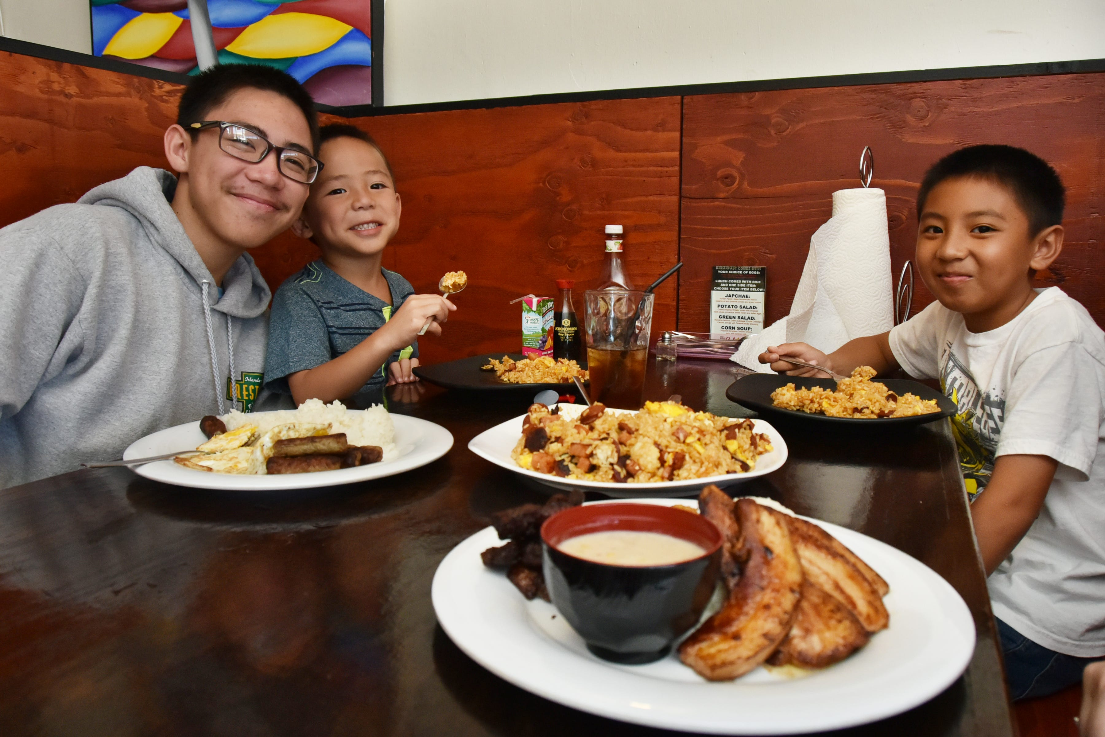 Kaleb, 16 (left); Roman, 5 (right); and Noah Sablan, 9 (opposite) enjoying their favorite dishes at The Cafeteria restaurant in Harmon in August 2015.