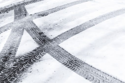 Automotive tire tracks on fresh wet snow.