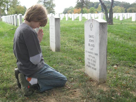 A Marine's grandson kneels at his headstone at Arlington National Cemetery.