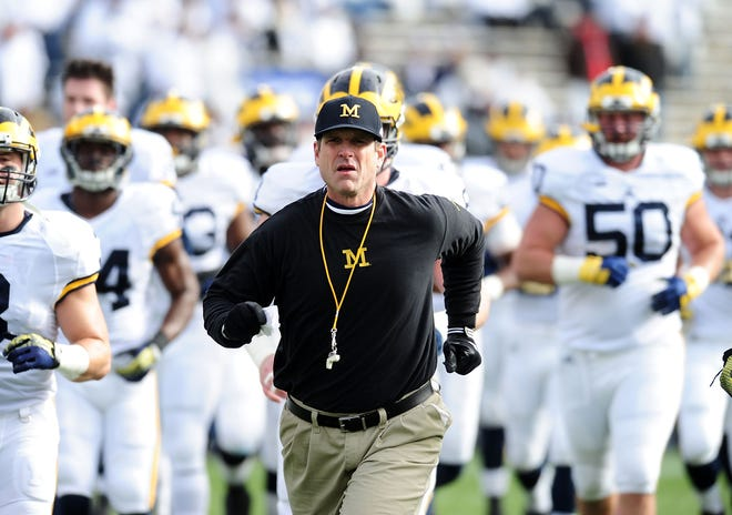 Michigan coach Jim Harbaugh runs onto the field prior to the game against Penn State at Beaver Stadium in Nov. 21, 2015.
