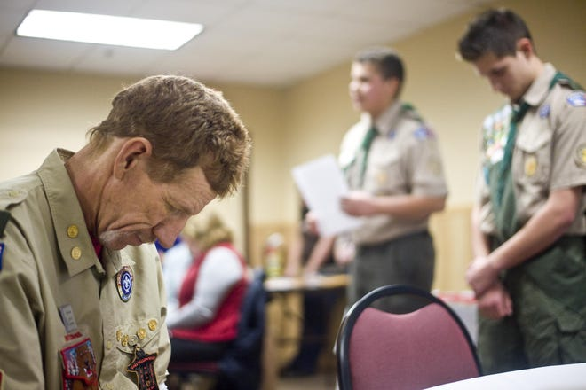 Paul Grosvold bows his head in prayer during a Boy Scouts court of honor meeting. Although the Montana Council of the Boy Scouts of America says scouting is safer than ever, the organization currently faces multiple lawsuits over sexual abuse lawyers say stretches back decades.