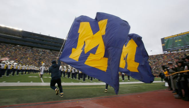Michigan cheerleaders run on the field with large Block M flags before their football game against Ohio State on Nov. 28, 2015, in Ann Arbor at Michigan Stadium.