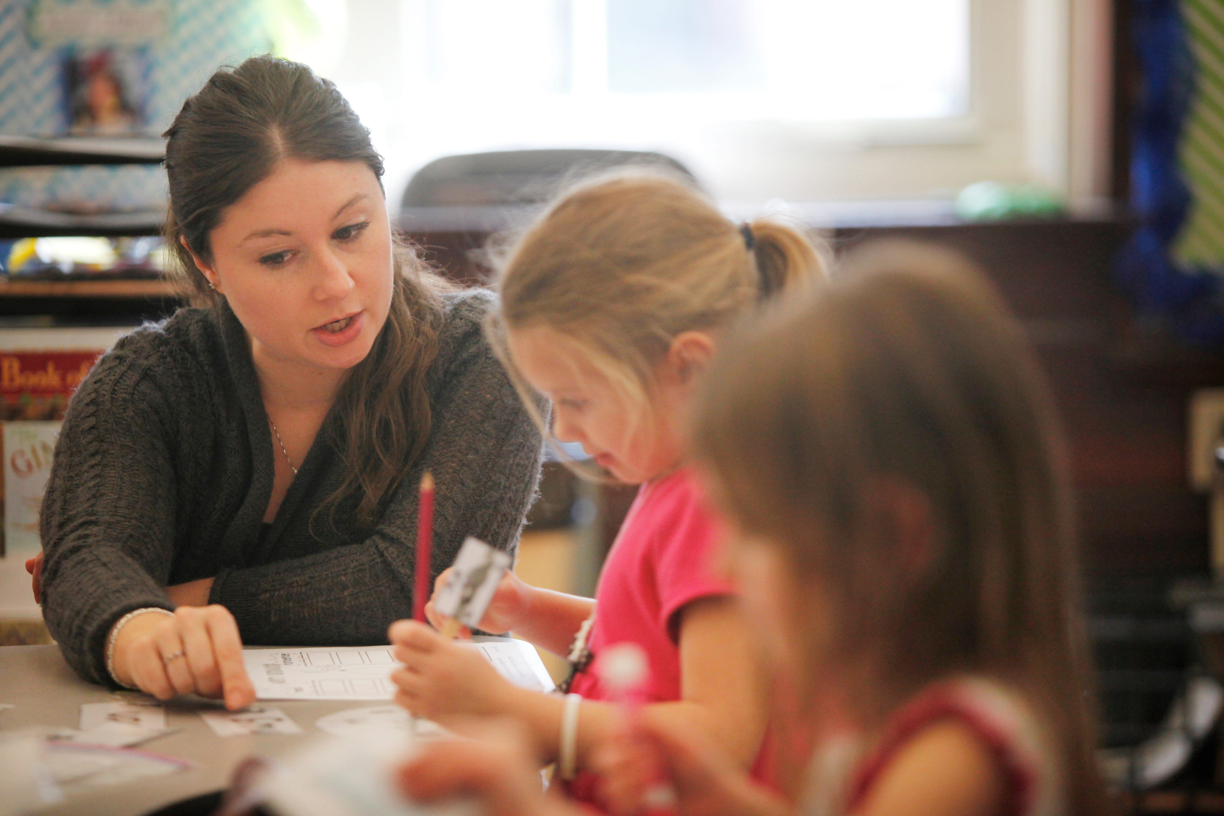 A staff member works with kindergarten students during a lesson at Bloom Elementary School, located in the Tyler Park neighborhood. Dec. 9, 2015.