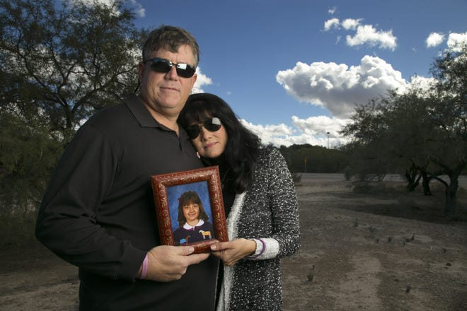 John and Roxanna Green hold a photograph of their daughter, Christina-Taylor Green, at the Christina-Taylor Green Memorial River Park in 2015.