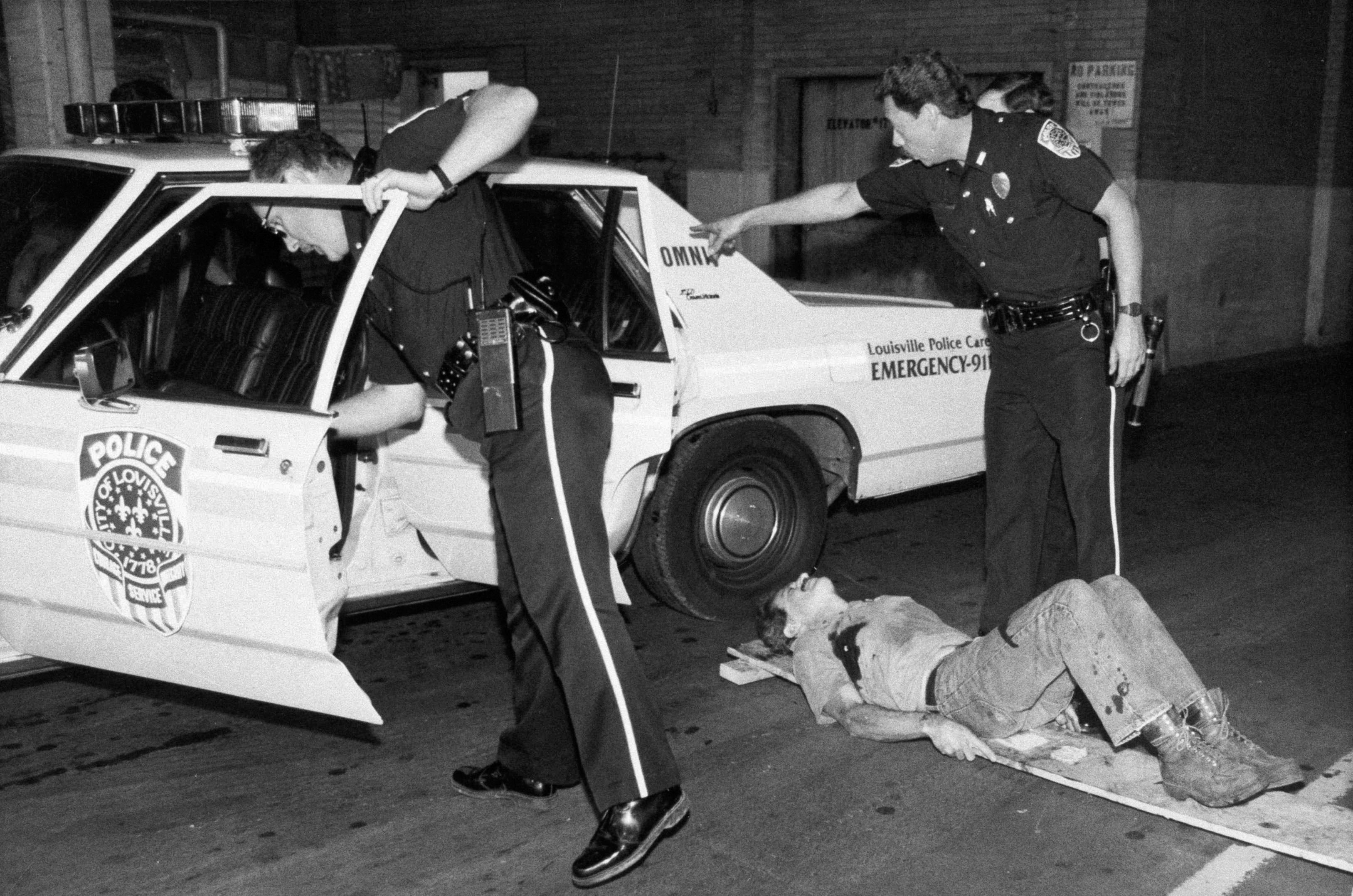 FILE - In this Sept. 14, 1989 file photo, Louisville police prepare to transport one of the victims of the Standard Gravure shooting spree in a police car in downtown Louisville, Ky. AP Photo/Bud Kraft