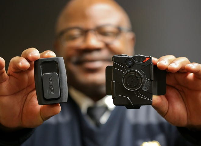Former Wilmington Police Inspector Elmer Harris holds the two body cameras — the VieVu (left) and TASER brands — that were tested by Wilmington police.