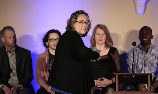 """Cincinnati Enquirer food critic Polly Campbell tosses her hat into the standing-room only crowd at The Phoenix during """"Storytellers"""", Wednesday, Feb. 3, 2016, at The Phoenix in Cincinnati."""
