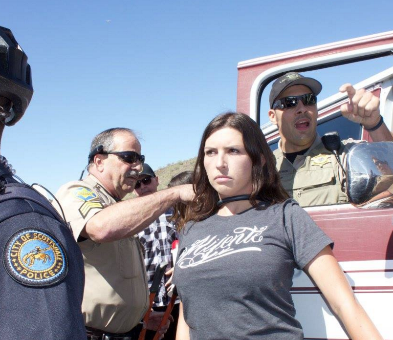 Jacinta Gonzalez locks her neck to a vehicle blocking the principal route of a rally for President Donald Trump in Phoenix.
