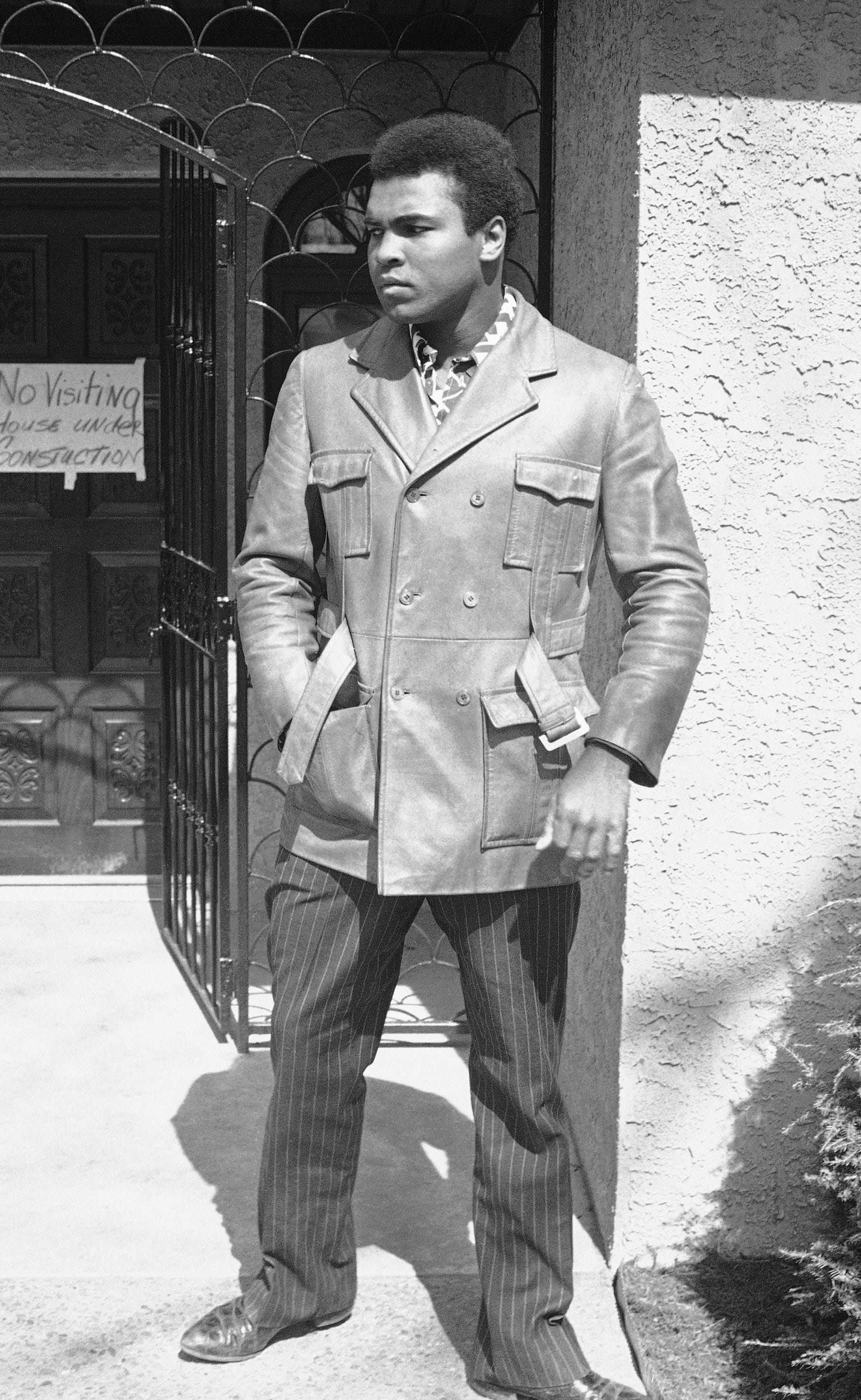 """Muhammad Ali, in 1971, waves from the doorway of his Cherry Hill home, where a sign on the door proclaims """"no visiting, house under construction."""""""
