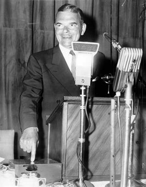 A Road Opened - Gov. Thomas E. Dewey presses button at Thruway banquet in Powers Hotel which flashed notice to toll collectors to start traffic. (Staff photo, 6/25/1954) DC 6/25/1954)
